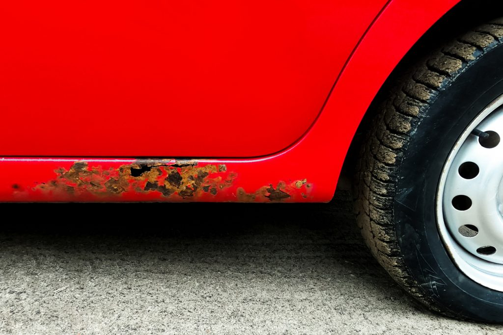 Rust on the body of the car. A view of the saeredi. Red. Fragment of the wheel.